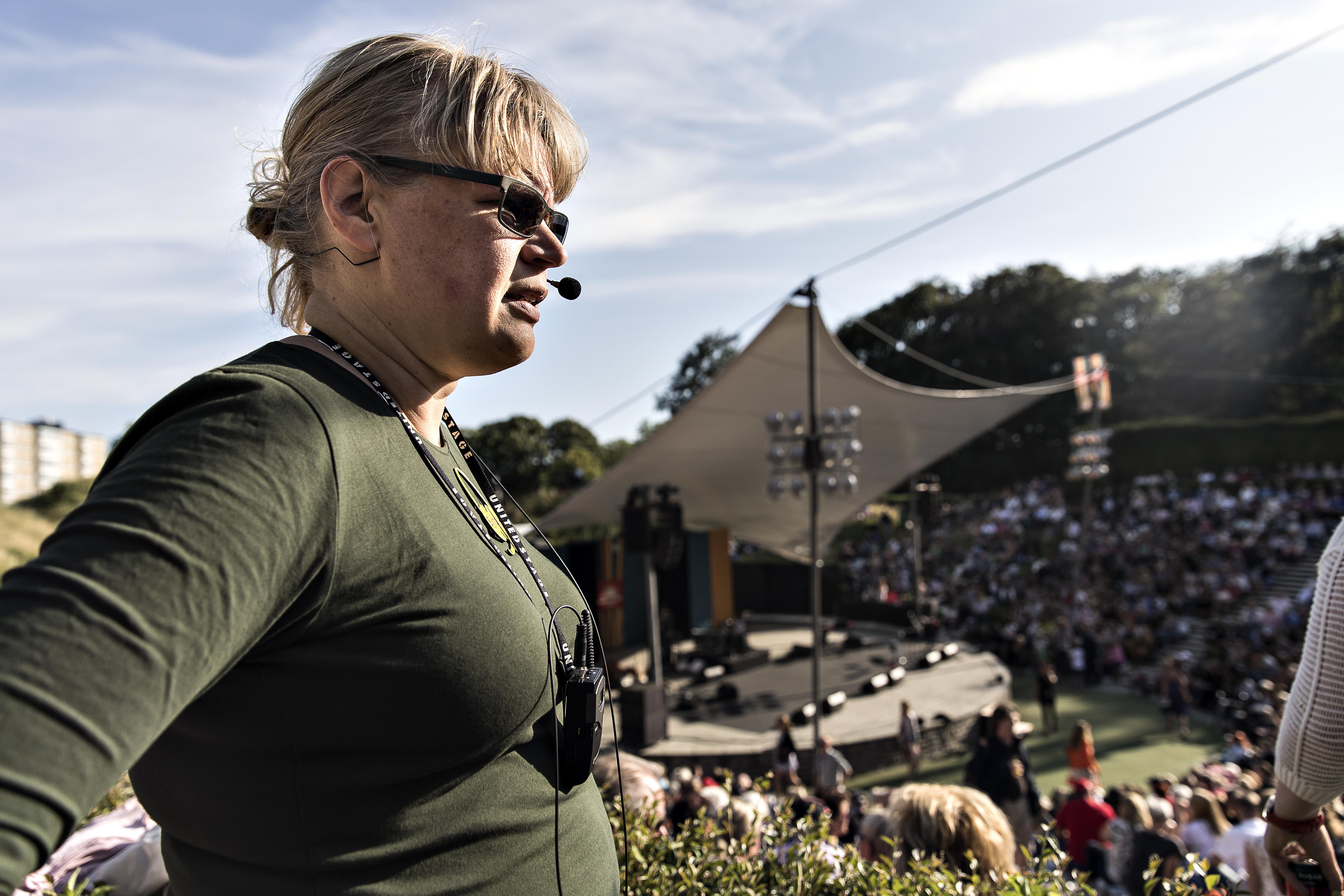 Jag med sändare och headsetmikrofon, framför en fullsatt utomhusteater och scen med segeldukstak..